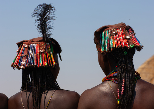 Muhacaona tribe women with kapapo headdress made of soda cans, Cunene Province, Oncocua, Angola