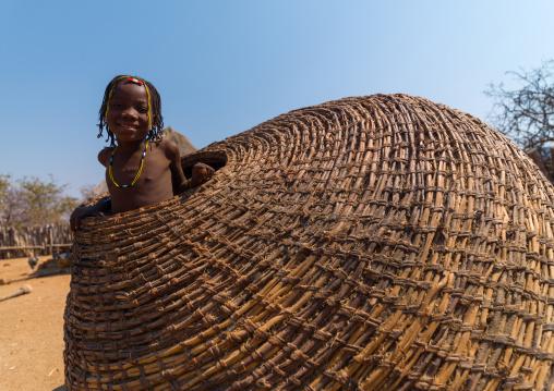 Muhacaona tribe girl inside a giant basket used to keep the corn, Cunene Province, Oncocua, Angola