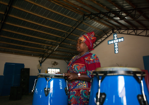 Angolan woman playing drums in a protestant church, Namibe Province, Namibe, Angola