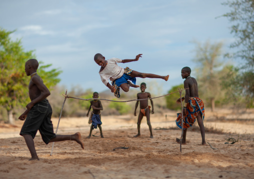 Mucubal tribe boys doing high jumping in the bush, Namibe Province, Virei, Angola