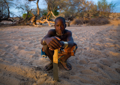 Mucubal tribe man with his machete sit in a dry river, Namibe Province, Virei, Angola