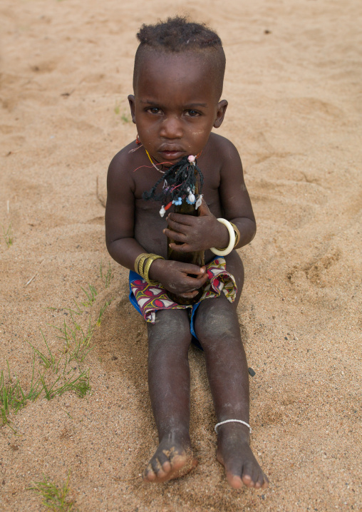 Mucubal tribe boy holding a doll made with a bottle beer, Namibe Province, Virei, Angola