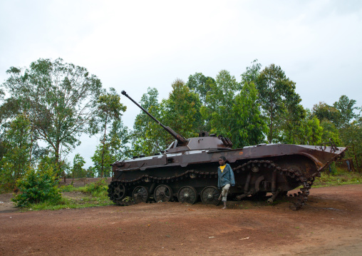 Angolan child standing in front of an old tank from the civil war, Bié Province, Kuito, Angola