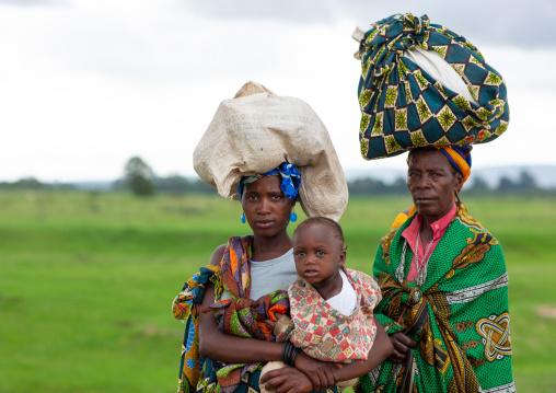 Women walking carrying sacks on head, Huila Province, Chibia, Angola