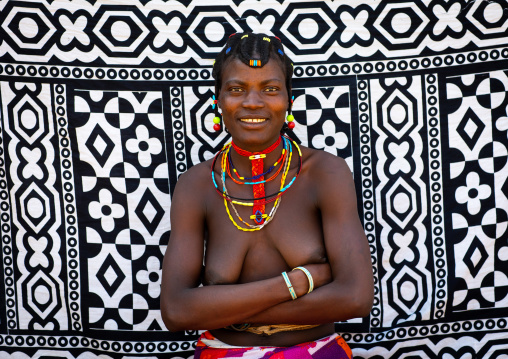 Portrait of a smiling mudimba tribe woman in front of a printed cloth, Cunene Province, Cahama, Angola