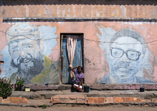 Woman in front of an old propaganda wall painting with Fidel Castro and Jose Eduardo dos Santos, Cunene Province, Cahama, Angola