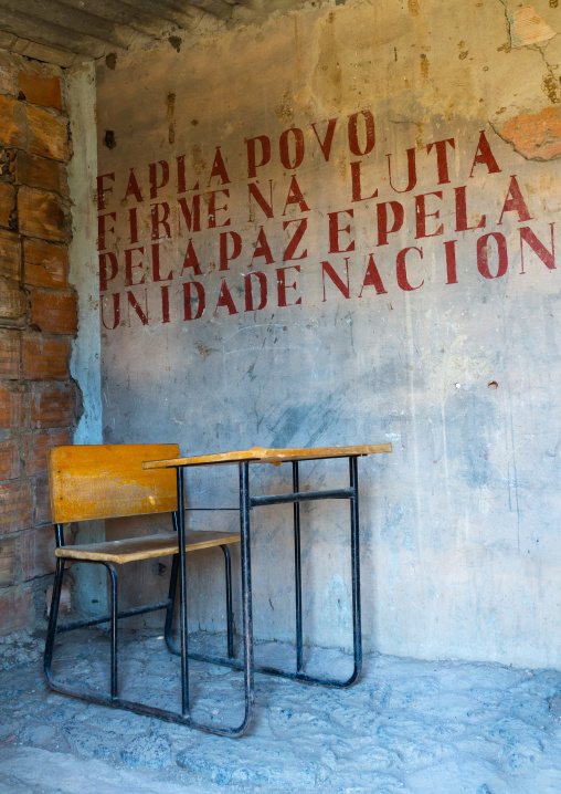 School desk in a classroom with old propaganda on the wall about forcas armadas populares de libertacao de angola popular armed, Cunene Province, Cahama, Angola