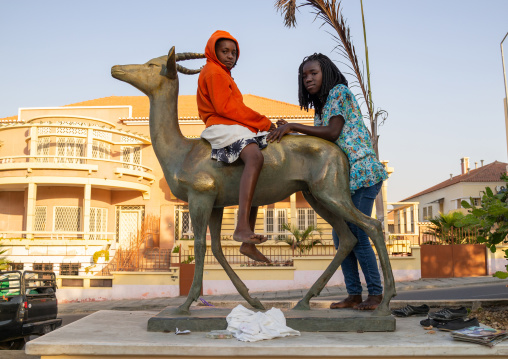 Angolan girls on a palanca negra statue in the street, Namibe Province, Namibe, Angola