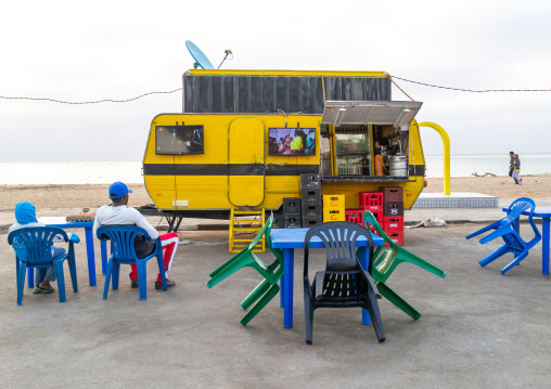 Angolan people watching television in a bar on miragens beach, Namibe Province, Namibe, Angola