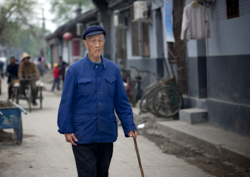 Chinese Man In Blue Clothes Walking With A Cane, Beijing China