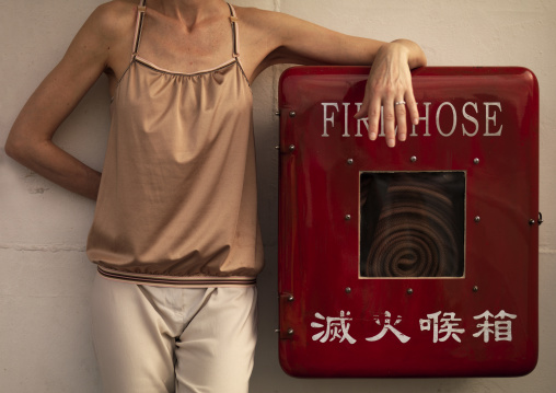 Woman Standing On Fire Hose On A Ferry, Hong Kong, China