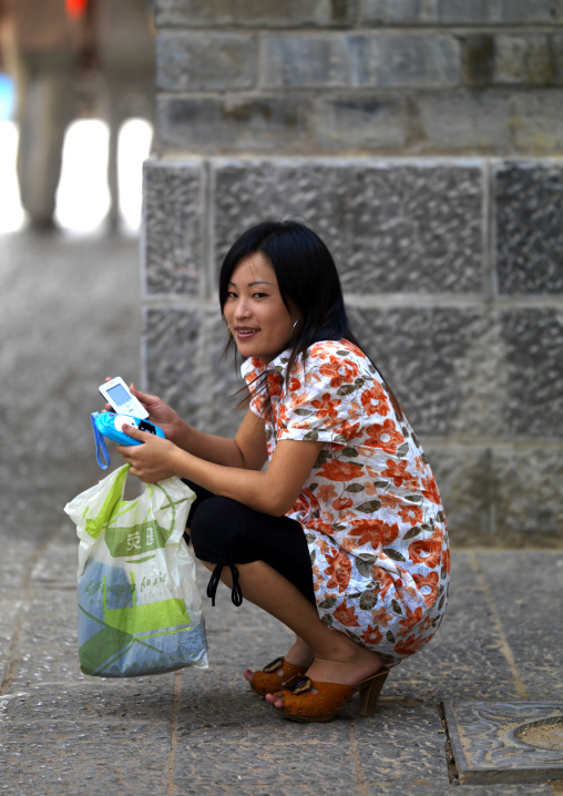 Young Woman With A Mobile Phone In The Street, Jianshui, Yunnan Province, China