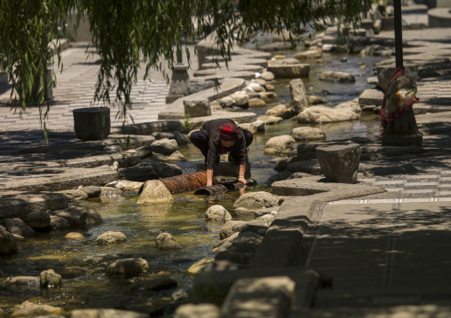Woman Washing Clothes In Dali River, Dali, Yunnan Province, China