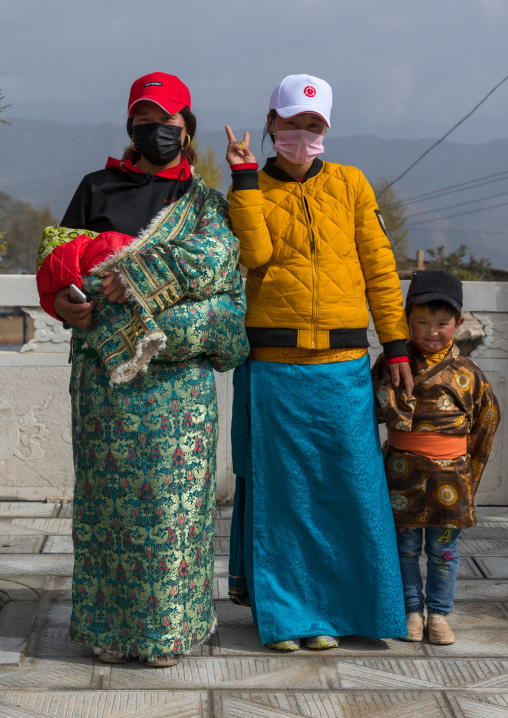 Tibetan pilgrims with traditional and modern clothes in Shachong monastery, Qinghai Province, Wayaotai, China