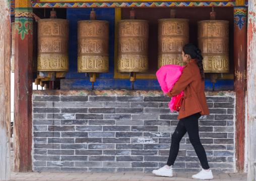 Tibetan pilgrim woman turning prayer wheels in Shachong monastery, Qinghai Province, Wayaotai, China