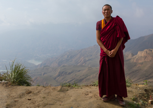 Portrait of a tibetan monk in Shachong monastery with the yellow river in the back, Qinghai Province, Wayaotai, China