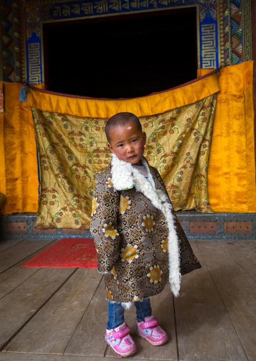 Tibetan child boy in traditional clothing in Shachong monastery, Qinghai Province, Wayaotai, China