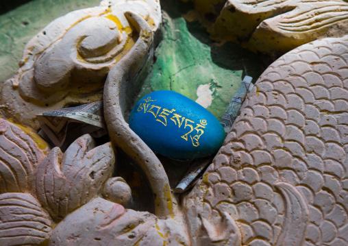 Tibetan religious budhist symbols carved on stones in Shachong monastery, Qinghai Province, Wayaotai, China