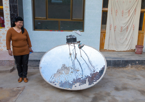 Salar ethnic minority woman in front of a solar energy cookery used to boil water, Qinghai province, Xunhua, China
