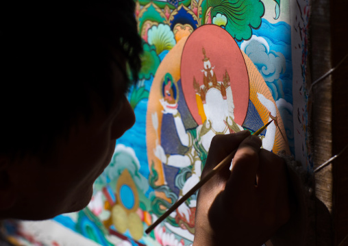 Tibetan artist painting a thangka at a workshop, Qinghai province, Wutun, China