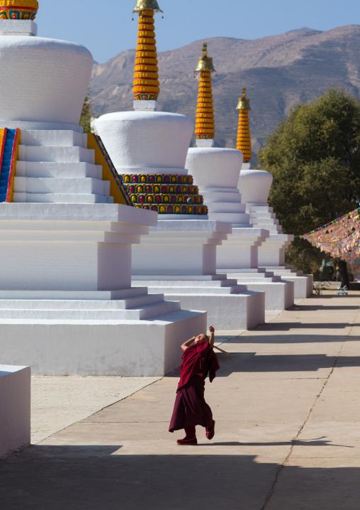 Young tibetan monk playing between the stupas in Wutun si monastery, Qinghai province, Wutun, China