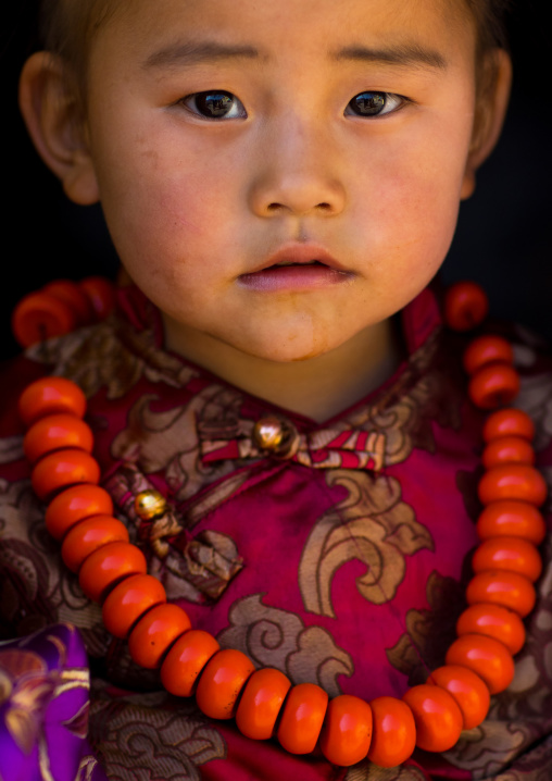 Tibetan child girl with a huge necklace, Tongren County, Rebkong, China