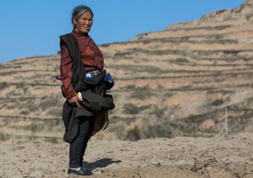 Old tibetan woman in the mountain, Tongren County, Rebkong, China