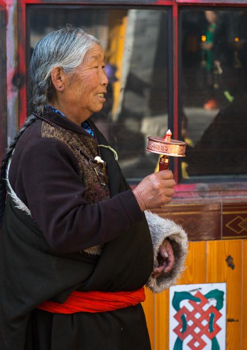 Tibetan pilgrim woman with a hand prayer wheel in Rongwo monastery, Tongren County, Longwu, China