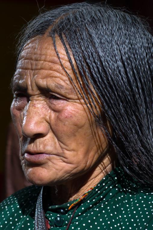 Tibetan pilgrim woman with braided hair in Rongwo monastery, Tongren County, Longwu, China
