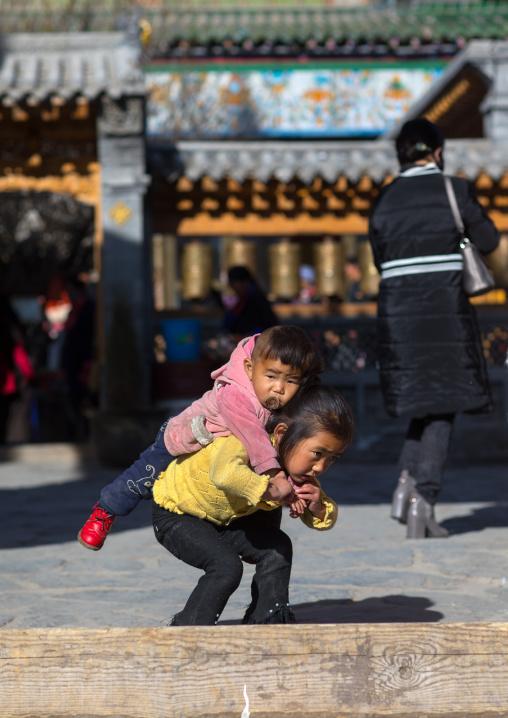 Tibetan girl carrying her brother on her back in Rongwo monastery, Tongren County, Longwu, China