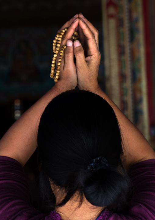 Tibetan pilgrim woman praying in Rongwo monastery, Tongren County, Longwu, China