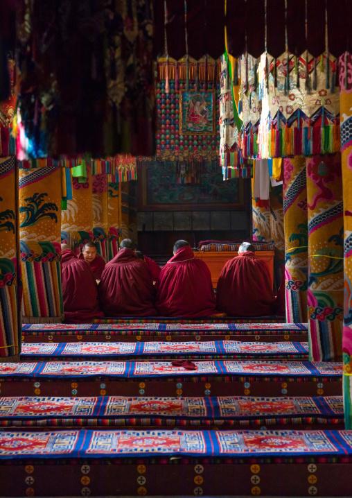 Monks praying and meditating inside Longwu monastery, Tongren County, Longwu, China