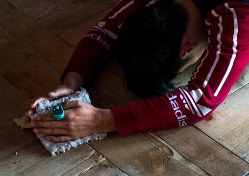 Tibetan pilgrim with mini hand tally counter praying and prostrating in Rongwo monastery, Tongren County, Longwu, China