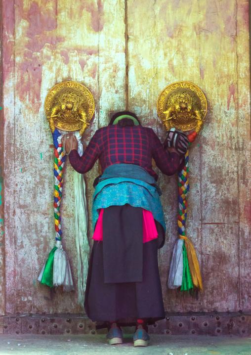 Tibetan woman praying in front of a traditional door in Rongwo monastery, Tongren County, Longwu, China