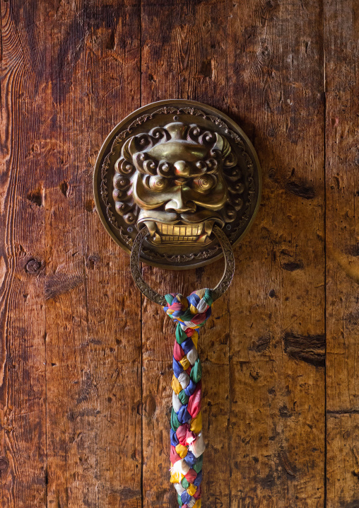Ornate knockers on traditional buddhist door temple in Rongwo monastery, Tongren County, Longwu, China