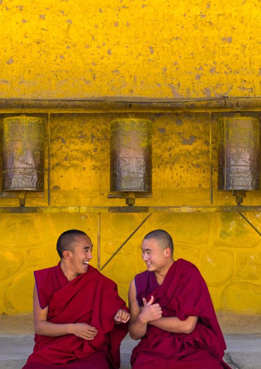 Monks debating in front of prayer wheels in a Rongwo monastery, Tongren County, Longwu, China