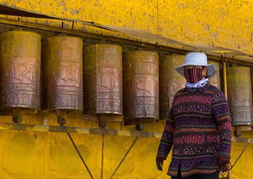 Tibetan pilgrim turning huge prayer wheels in Rongwo monastery, Tongren County, Longwu, China