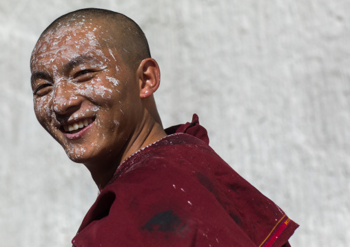 tibetan Monk with white painting on his face while renovating the walls of a temple in Rongwo monastery, Tongren County, Longwu, China