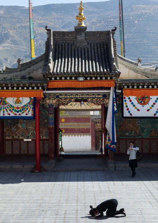 Tibetan woman praying in the middle of the temple courtyard in Rongwo monastery, Tongren County, Longwu, China