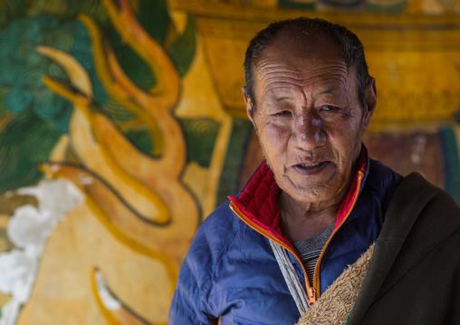 Tibetan pilgrim man in Rongwo monastery, Tongren County, Longwu, China