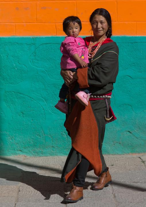 Tibetan pilgrim mother with her child in Rongwo monastery, Tongren County, Longwu, China