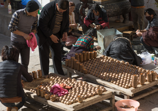 Volunteers cleaning butter lamps in Rongwo monastery, Tongren County, Longwu, China