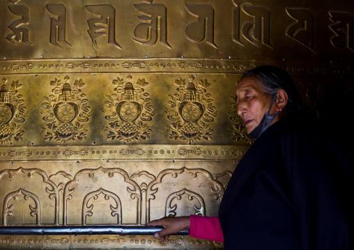 Tibetan pilgrim turning huge prayer wheel in Rongwo monastery, Tongren County, Longwu, China