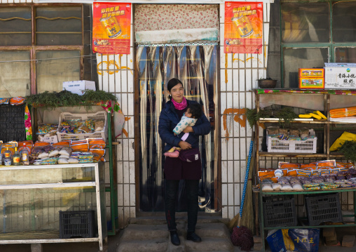 Tibetan woman with her baby in front of a shop, Tongren County, Longwu, China