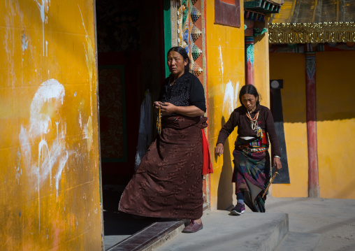 Tibetan women turning prayer wheels in a Rongwo monastery, Tongren County, Longwu, China