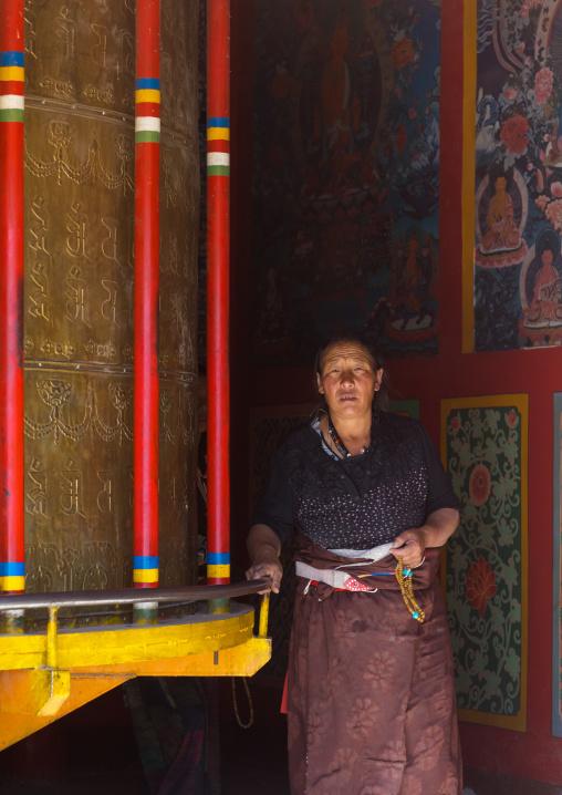 Tibetan woman turning prayer wheels in a Rongwo monastery, Tongren County, Longwu, China