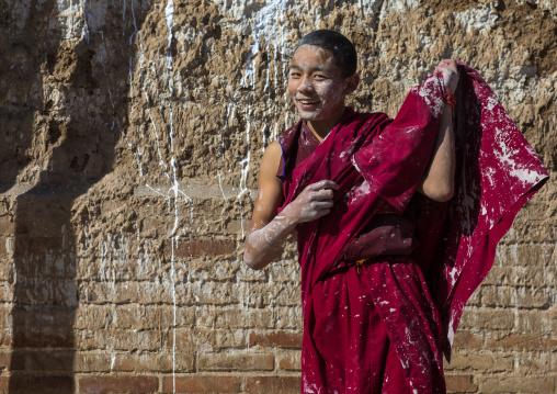 Tibetan monk enjoying a water fight after the yearly renovation of the Rongwo monastery, Tongren County, Longwu, China