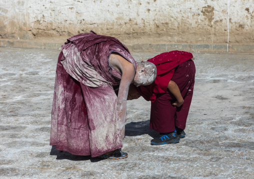 Tibetan monks enjoying a water fight after the yearly renovation of the Rongwo monastery, Tongren County, Longwu, China