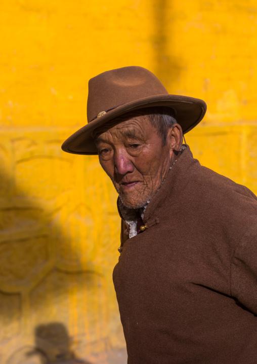 Old tibetan pilgrim man with a hat in Rongwo monastery, Tongren County, Longwu, China