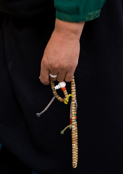 A tibetan pilgrim fingers her prayer beads in Rongwo monastery, Tongren County, Longwu, China